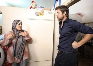 Brad Bitt listening to a mother during his visit with his wife to Syria to check on Iraqi refugees on October 2nd 2009